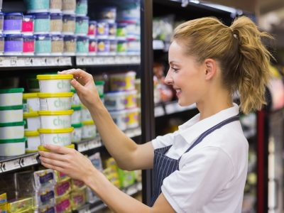 Smiling blonde worker taking a products in shelf
