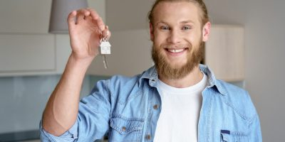 Young excited happy bearded man student guy buyer broker agent sell give show hold keys own new modern flat apartment smile confident look at camera background home real estate concept, portrait.